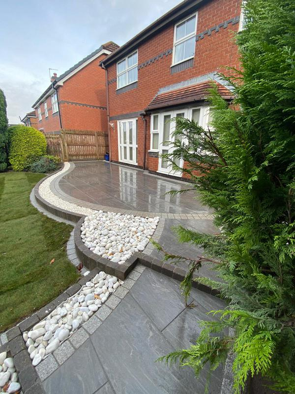 Image 2 - Porcelain paving project wins granite setts as a border. Three different levels with a curved stepped runway down to the seating area with pergola