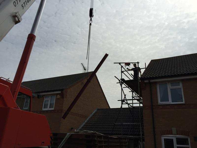 Image 44 - Crane lifting new metal beam for structure in loft