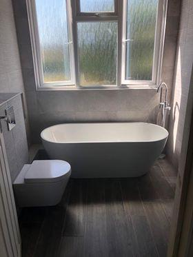 Image 5 - Fully designed and installed modern bathroom with free standing bath and tap and 2 different types of wall tiles.
