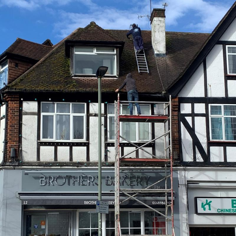 Image 33 - the team half way from removing moss of the roof of shop