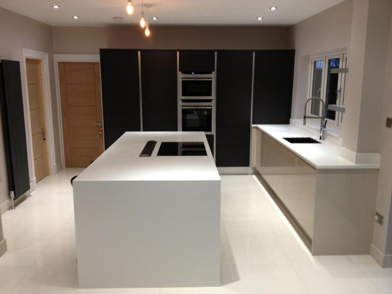 Image 77 - Kitchen installed with Black True Handleless tall units combined with lighter handleless base units and white Corrin worktops.