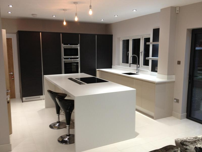 Image 78 - Kitchen installed with Black True Handleless tall units combined with lighter handleless base units and white Corrin worktops.