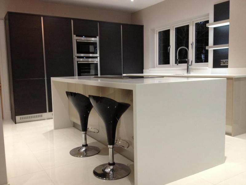 Image 79 - Kitchen installed with Black True Handleless tall units combined with lighter handleless base units and white Corrin worktops.