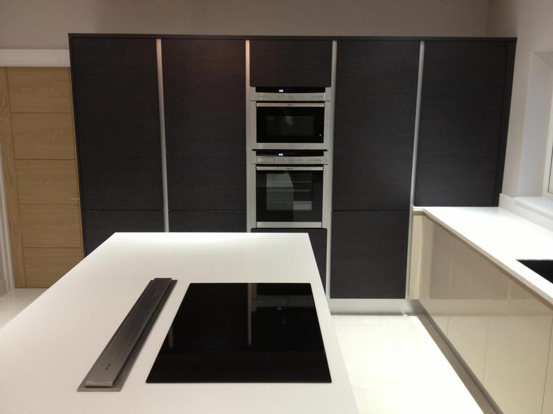 Image 80 - Kitchen installed with Black True Handleless tall units combined with lighter handleless base units and white Corrin worktops.