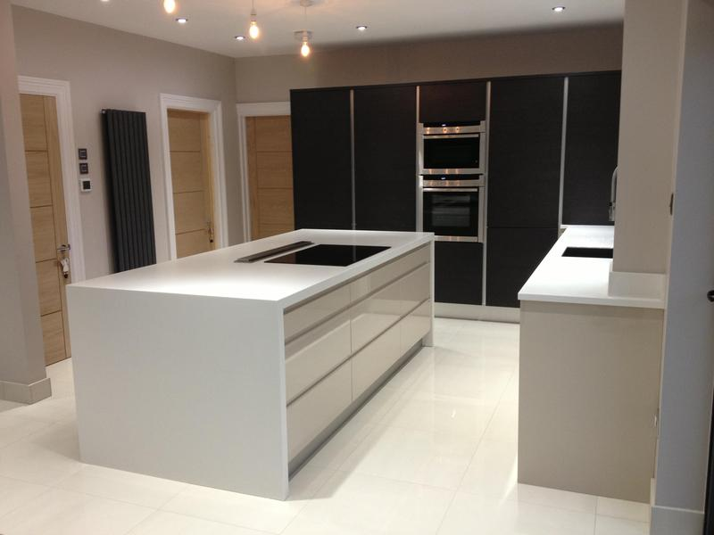 Image 81 - Kitchen installed with Black True Handleless tall units combined with lighter handleless base units and white Corrin worktops.