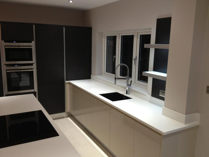 Image 82 - Kitchen installed with Black True Handleless tall units combined with lighter handleless base units and white Corrin worktops.