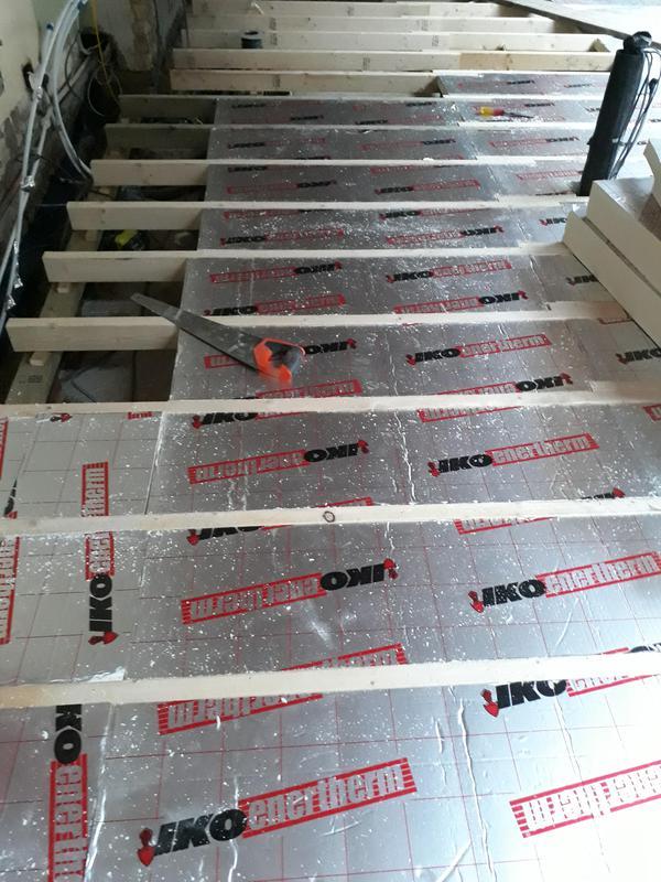 Image 30 - Installation of insulation in between joists of floating floor.