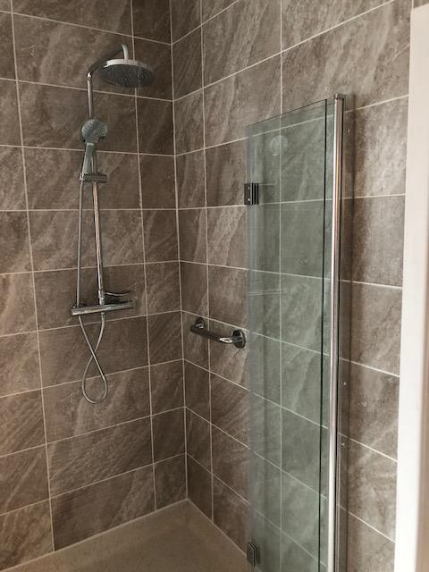 Image 14 - Wet floor shower room, full tiling, thermostatic shower with fixed head, chrome rail and bi fold glass shower screen folded back.