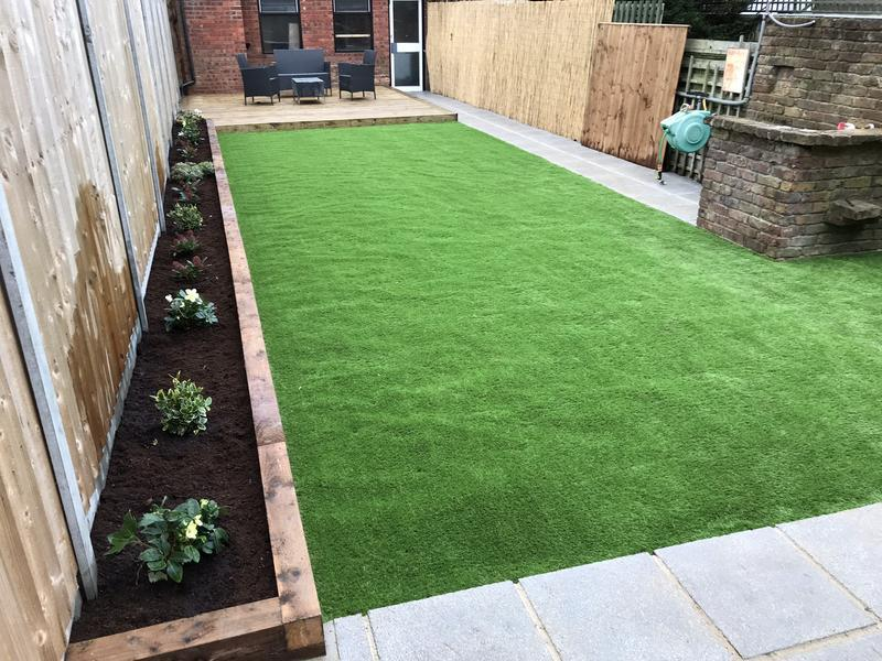Image 49 - Artificial grass, raised flower beds, decking, paved pathway and small patio.