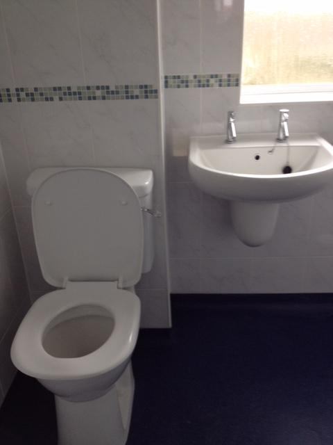 Image 3 - Raised toilet pan & cistern, wash hand basin and semi ped, full tiling with border and anti slip flooring.