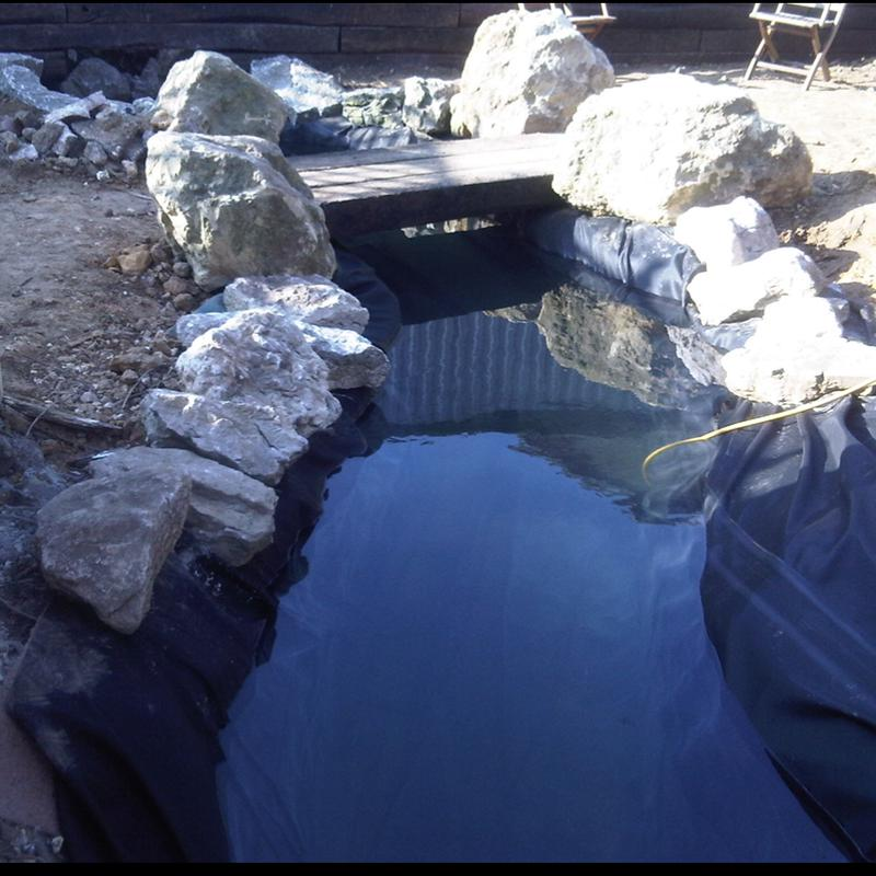 Image 24 - A koi pond we built, the spec was, it had to look like a river running across the width of the garden, and have a bridge