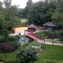 Image 2 - Large decked area 15m x 7.5m and 5m raised off the edge of a hill. Patio and pathway with timber bridge.