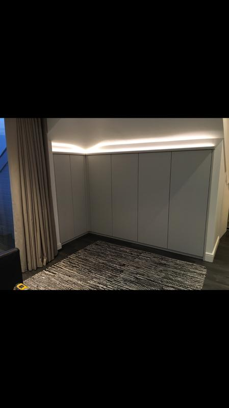 Image 2 - Bespoke wardrobe built beneath awkward ceiling pitch . With dimmable pelmet lighting.