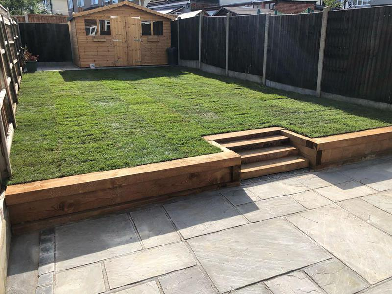 Image 35 - Grey sandstone patio with sleepers retaining wall that incorporates some lovely decorative steps to a lush new lawn. (turf)