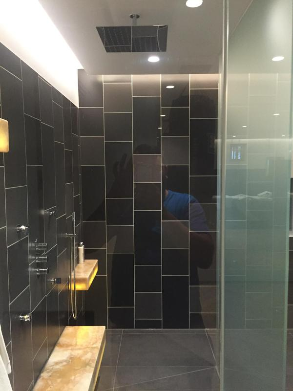 Image 20 - A stylish walk in shower room with large wall tiles and a square hung shower head.