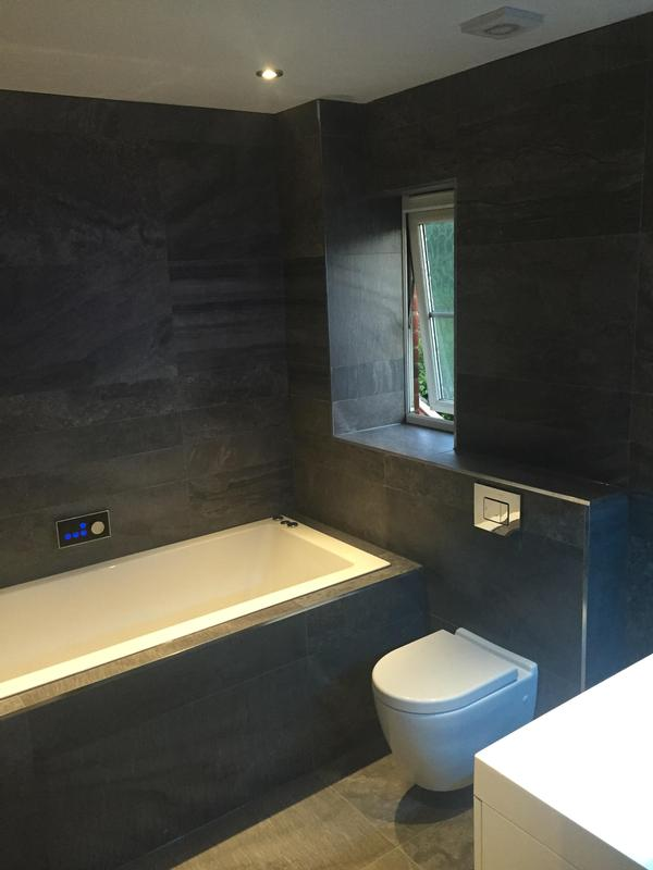 Image 15 - This dark tiled bathroom has a digital bath filler with just the touch of a button.