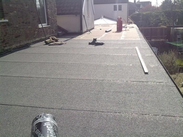 Image 32 - New flat roof getting applied of green mineral torch on felt