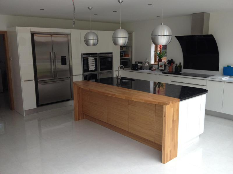 Image 2 - Bespoke top handle kitchen installed with custom made oak breakfast bar and plinth lighting.