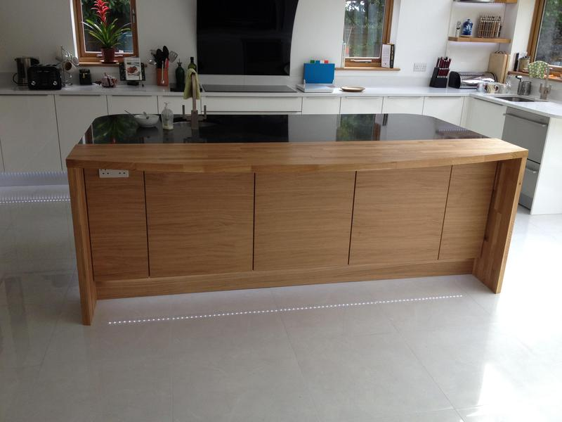 Image 7 - Bespoke top handle kitchen installed with custom made oak breakfast bar and plinth lighting.