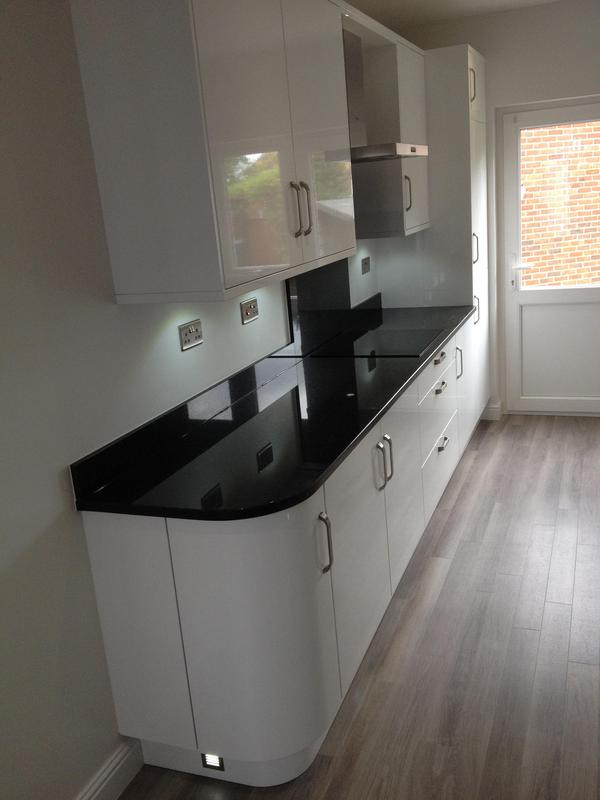 Image 20 - Gloss white slab kitchen installed as part of a full refurbishment with black quartz worktops and Karndean Flooring.