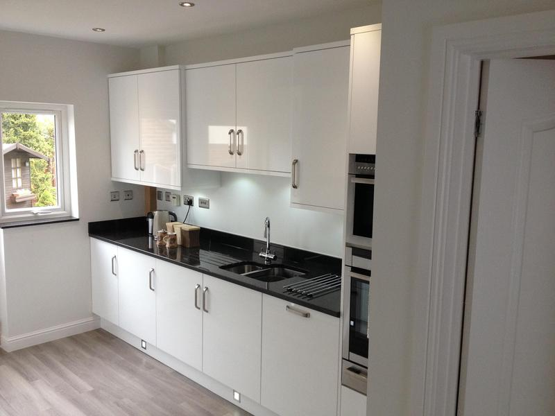Image 21 - Gloss white slab kitchen installed as part of a full refurbishment with black quartz worktops and Karndean Flooring.