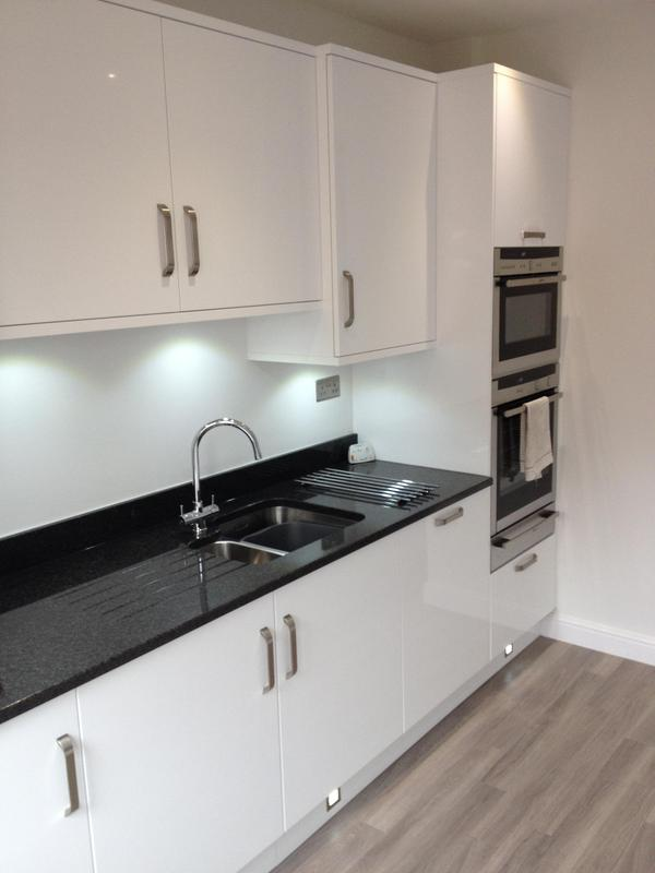 Image 22 - Gloss white slab kitchen installed as part of a full refurbishment with black quartz worktops and Karndean Flooring.