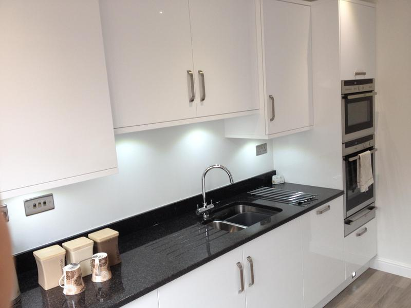 Image 23 - Gloss white slab kitchen installed as part of a full refurbishment with black quartz worktops and Karndean Flooring.
