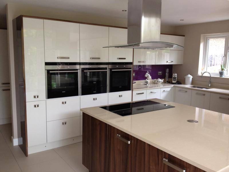 Image 88 - Two tone gloss kitchen installed with a plinth lighting and a bespoke crackle glaze glass breakfast bar.