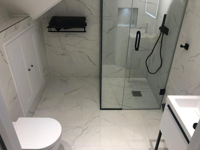 Image 40 - Marble effect en suite shower room with built in storage for a spacious room and a wall hung towel rack.