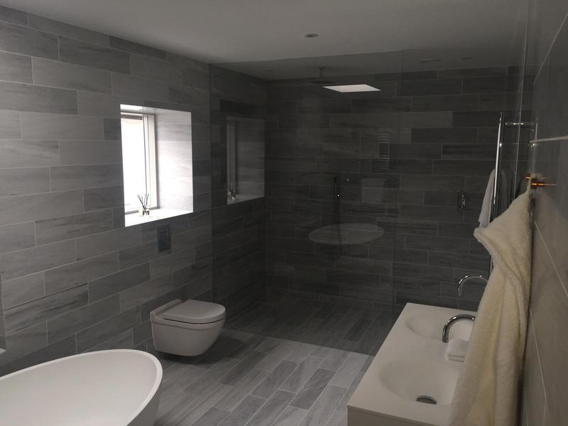 Image 35 - Large wet room shower with square style basin and wall hung toilet. Finished with large grey wall tiles.
