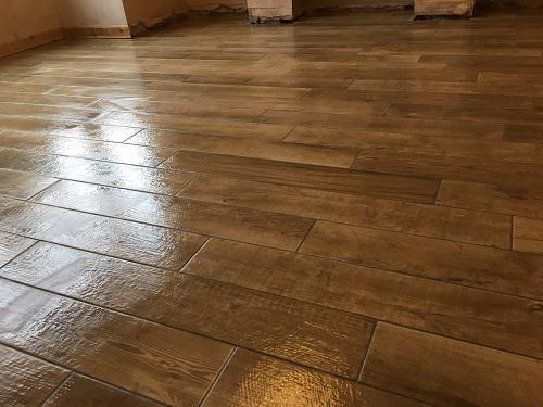 Image 192 - 65 m2 of flooring... kitchen diner/hall/toilet and snug. All tiled in porcelain wood effect plank tiles and grouted in smoke