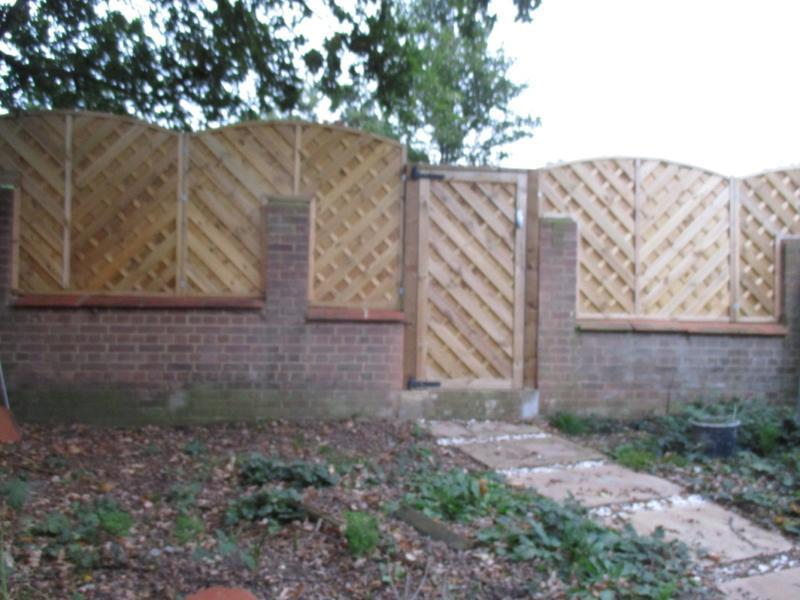 Image 35 - New fencing and gate cut into a rear brick wall.